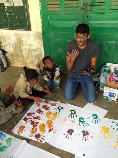 Un volontaire et des enfants peignent avec leurs mains lors d'une mission humanitaire