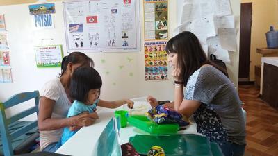 Un stagiaire en kinésithérapie travaille avec un patient au centre de réhabilitation où a lieu le projet de construction de court terme de Projects Abroad