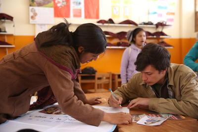 Un volontaire travaille avec un professeur local sur les objectifs du plan d'action de l'établissement partenaire