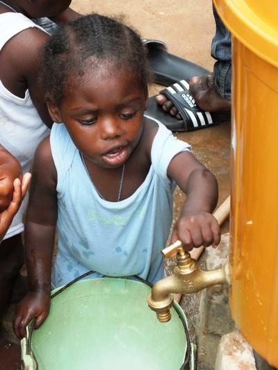 Une jeune fille utilise un robinet fabriquer par les volontaires lors d'une mission humanitaire dans un établissement partenaire au Togo