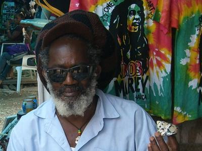 Un Rastafari jamaïcain pose devant une t-shirt de Bob Marley