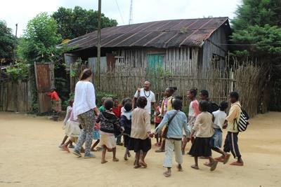 Une volontaire en mission humanitaire joue dans le cours avec des enfants à Madagascar
