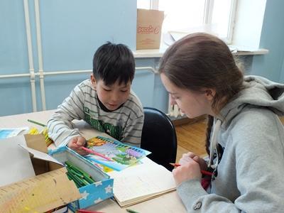 Une volontaire enseignant à un enfant dans le cadre du chantier humanitaire et communautaire