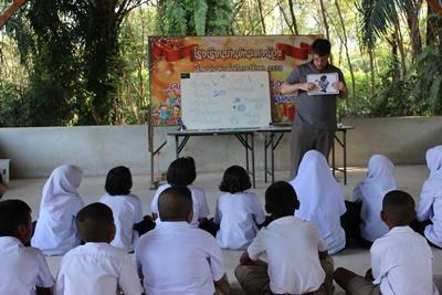 Les enfants d'une classe écoutent un volontaire donnant un cours d'anglais