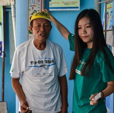 Une volontaire en campagne de sensibilisation et de soins de santé relève la taille d'un local aux Philippines