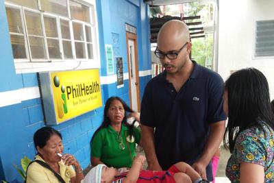 Un volontaire pèse un bébé lors d'une campagne de soins en santé et médecine