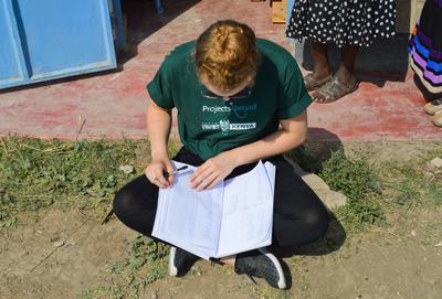 Une volontaire relie ses notes lors de son stage en pharmacie en tant que bénévole à l'étranger