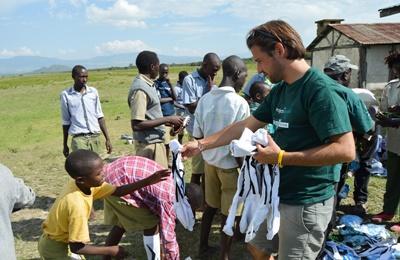 Un volontaire en mission humanitaire de courte durée distribue des uniformes à des enfants au Kenya