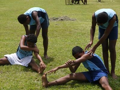 Teenage students do exercises before their track & field session at school.
