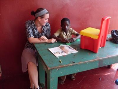 Une volontaire aide un enfant à travailler dans une classe ne Jamaïque