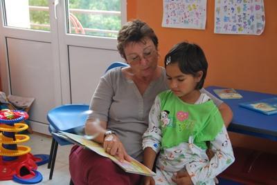 Une volontaire professionnelle  lit un livre à un enfant à l'hôpital, près de Brasov