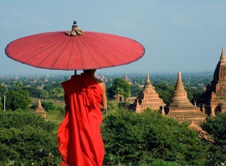 Un moine bouddhiste contemple un paysage de temples anciens en Birmanie, en Asie.