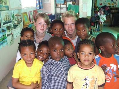 Deux volontaires en mission humanitaire en Afrique du Sud avec un groupe d'enfants