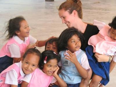 Une volontaire joue avec des enfants lors de sa mission humanitaire en Asie en Thaïlande