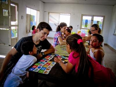 Un jeune homme en service volontaire international en Argentine joue avec des enfants en classe