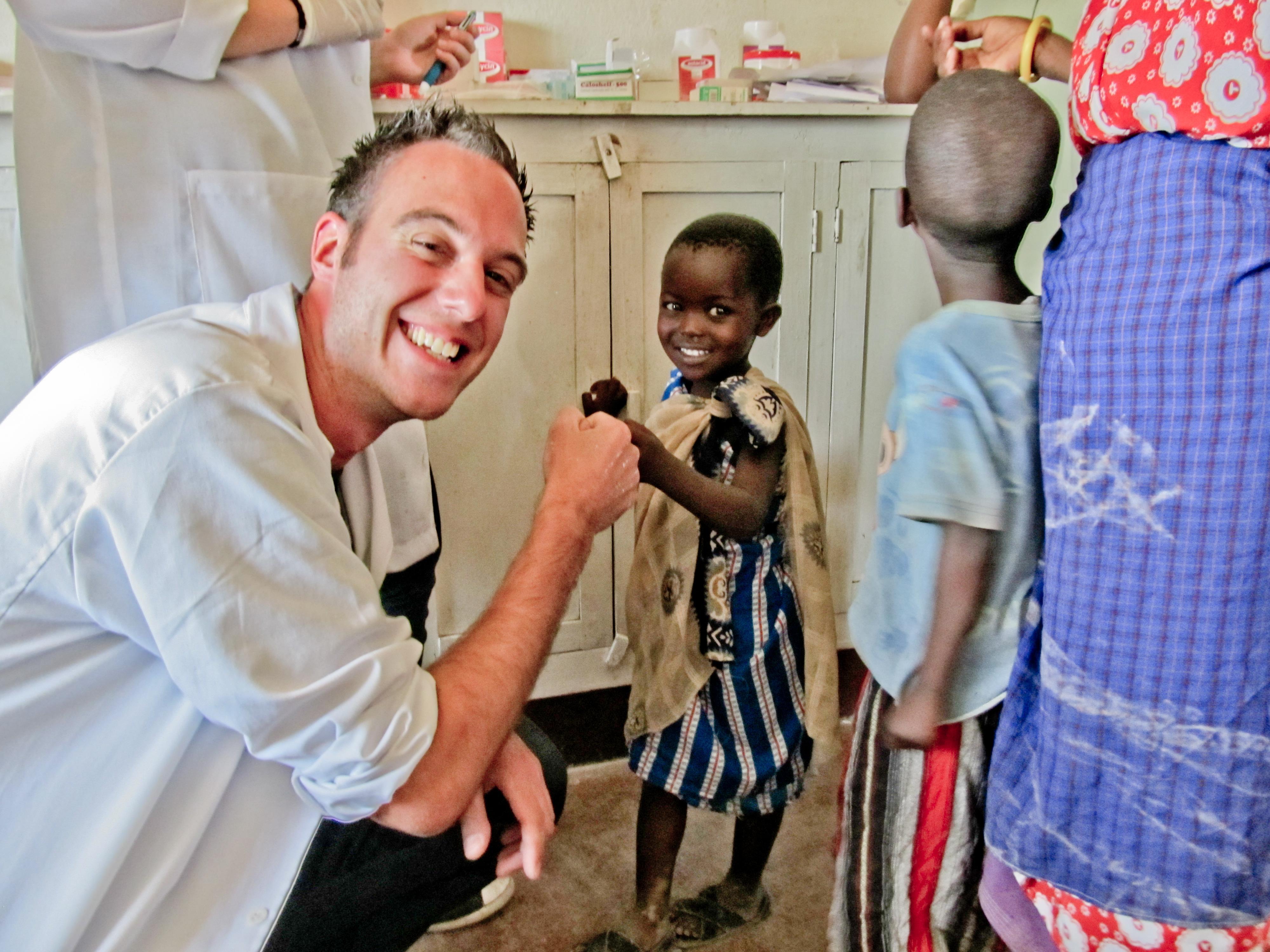 un volontaire en voyage solidaire de médecine avec un enfant souriant en Tanzanie